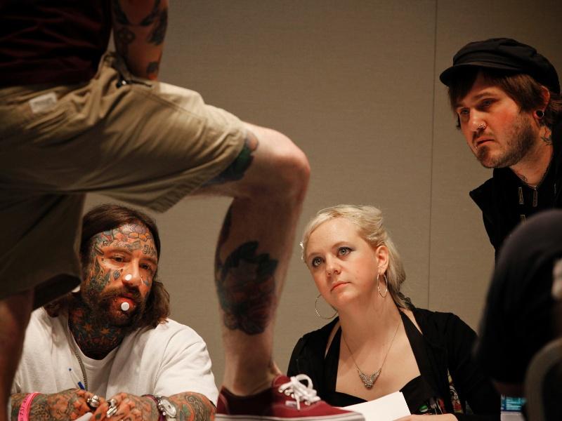 2.mar.2012 - Juízes inspecionam tatuagens no Festival de Hampton Roads Tattoo, na Virgínia (EUA)