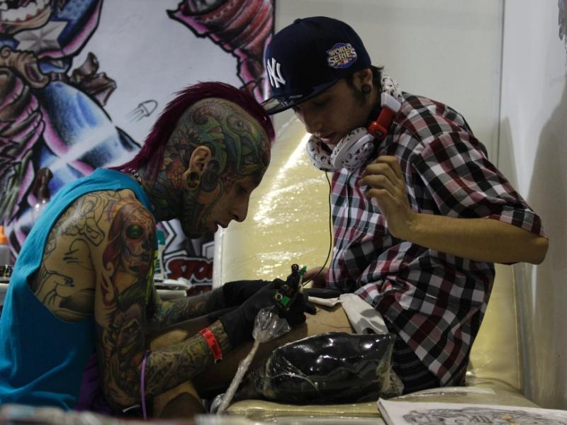 9.jun.202 - Homem tatua jovem durante convenção de tatuagens em Bogotá (Colômbia)