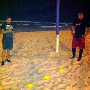Acompanhado de um fisioterapeuta, Adriano descansa durante intervalo de treino físico na praia