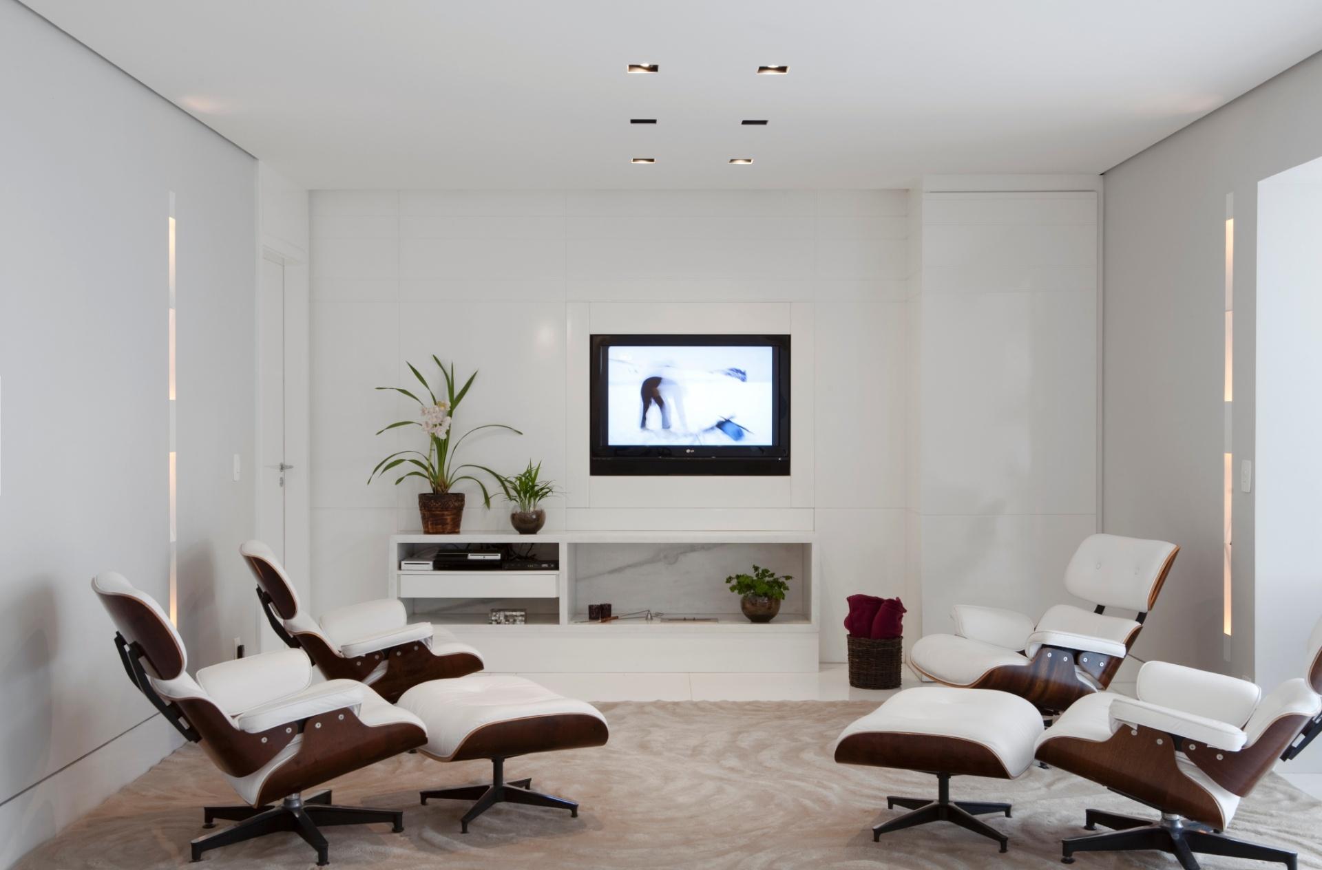 Apenas o tapete da Século, na cor bege, quebra com a unidade do branco proposto pela arquiteta Cristina Menezes no home theater. As  poltronas Charles Eames, da Tetum, trazem sofisticação e design ao ambiente