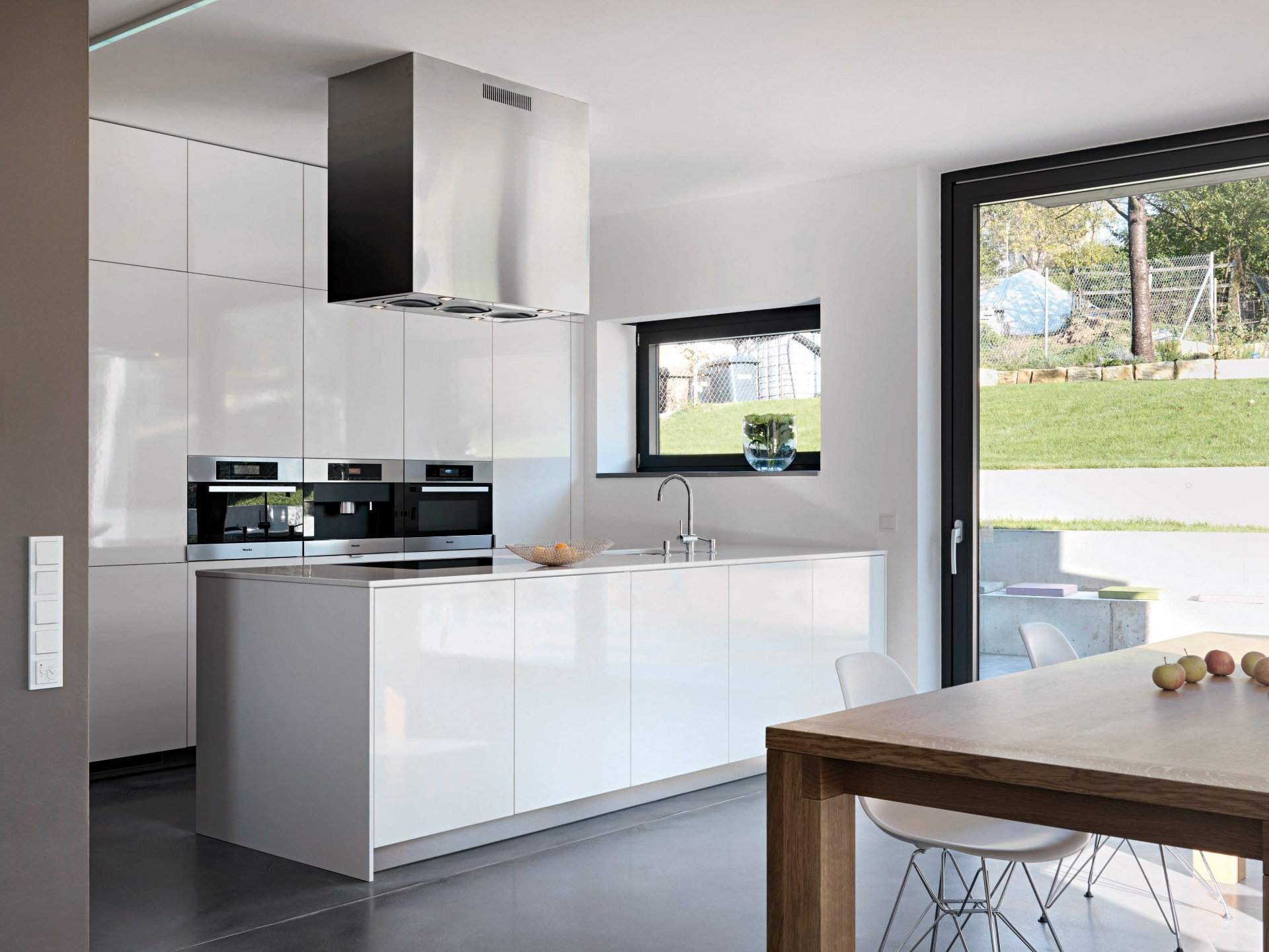 Integrada ao ambiente de jantar, a cozinha assinada pelos arquitetos alemães, Gunter Fleitz e Peter Ippolito, usou mobiliário da Leicht que se destaca sobre o piso acinzentado, e contrasta com a mesa em madeira. Aqui, o branco também tem a função de garantir limpeza