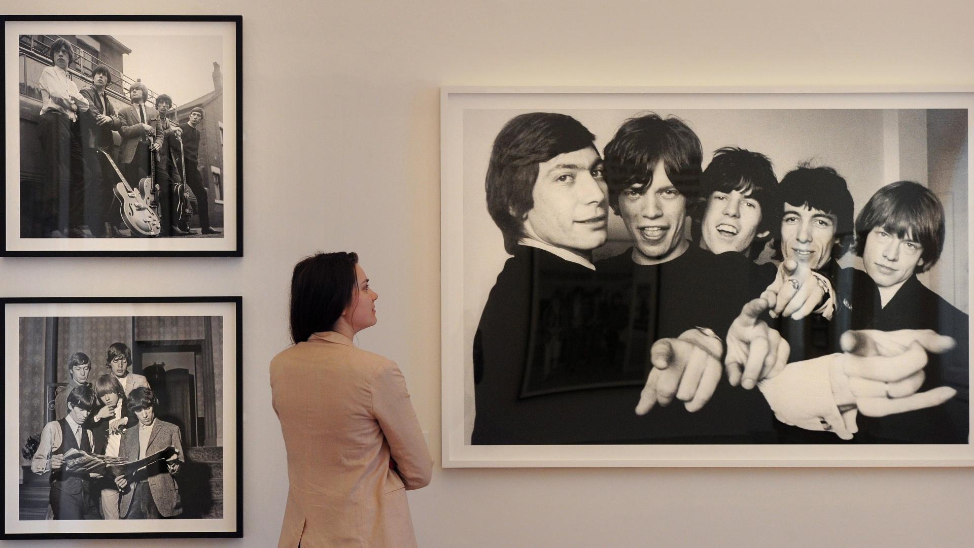 Mulher observa foto dos Rolling Stones na exposição