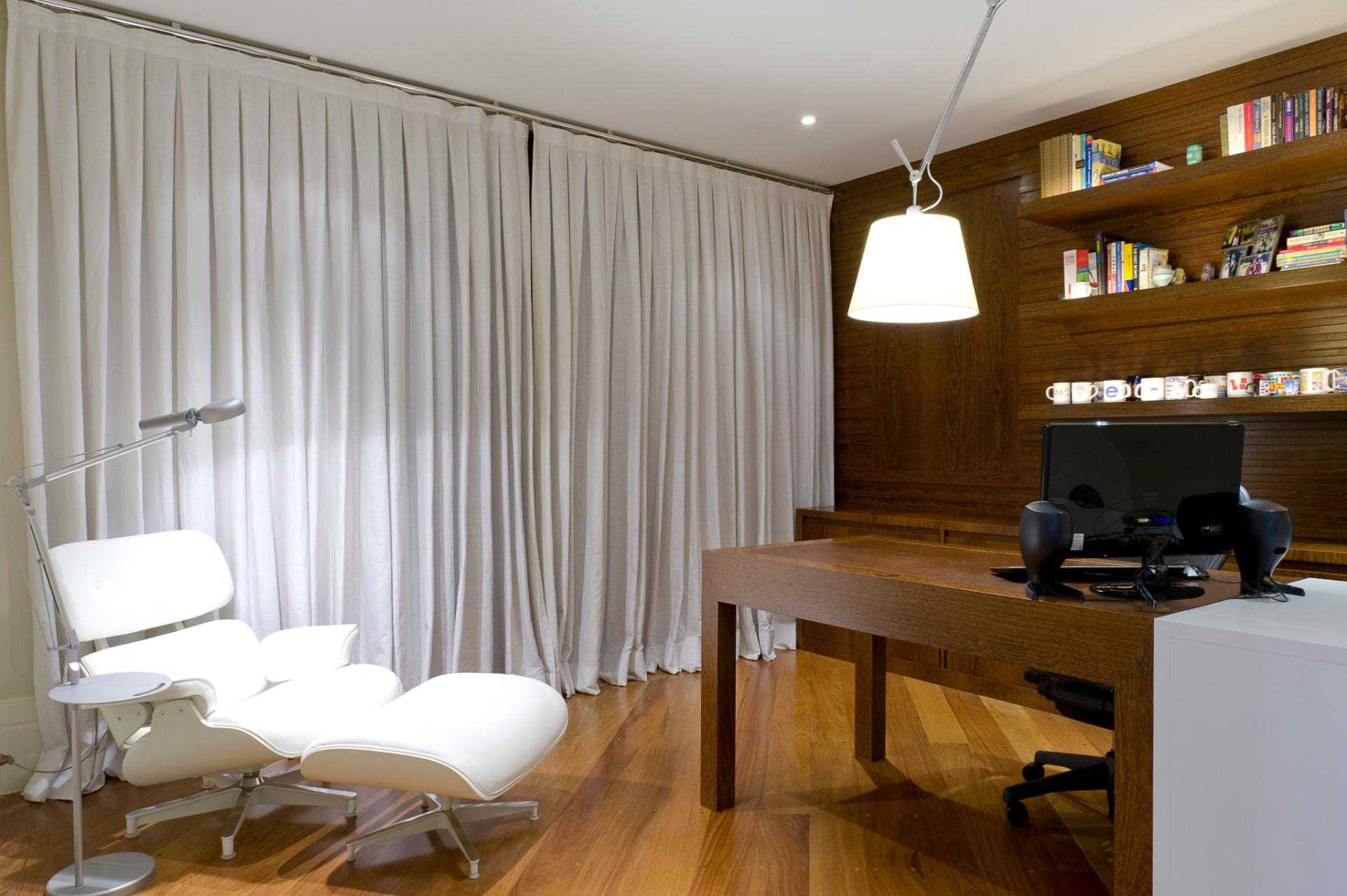 Na proposta do arquiteto Gustavo Motta para o home office de 15,50 m², equilíbrio entre a neutralidade da cor e o calor da madeira e do couro. A cortina em linho, da Casa Vestida, destaca o mobiliário executado pela Móveis Trettel. Já a poltrona Charles Eames, da Brentwood, se destaca no contexto devido à iluminação