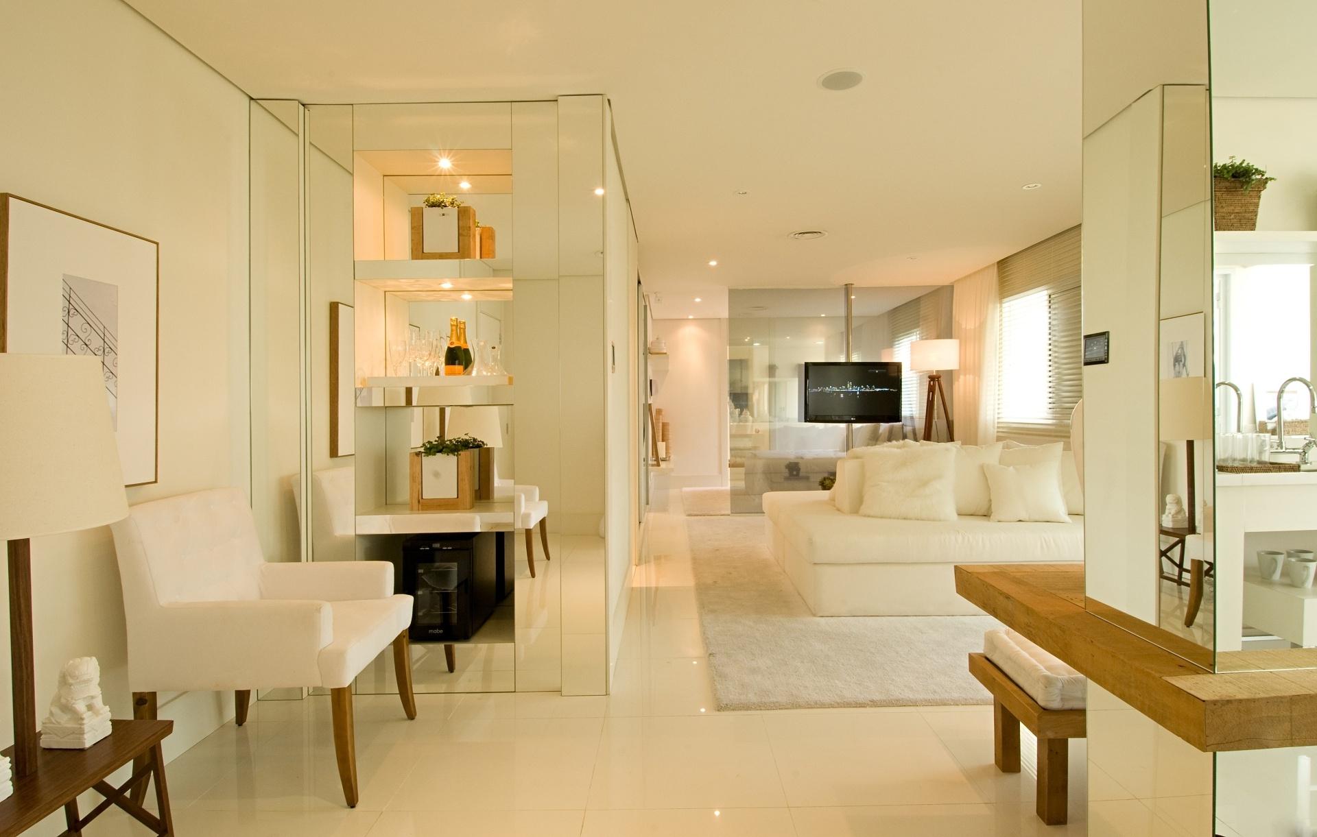 O jogo de espelhos e os revestimentos de piso e parede brancos deram unidade ao imóvel planejado pela arquiteta Débora Aguiar, que também optou por mobiliário, no mesmo tom, em contraponto à madeira