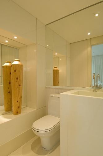 Os revestimentos e louças claras, em conjunto com os espelhos, ampliaram o pequeno lavabo planejado por Débora Aguiar