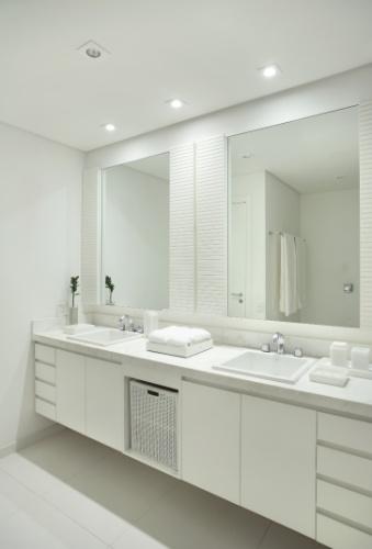 Para atender a solicitação dos clientes por um banheiro claro e amplo, a arquiteta Carla Dichy optou por mármore no tampo e nos revestimentos, e os armários e na cuba, optou pelo tom branco