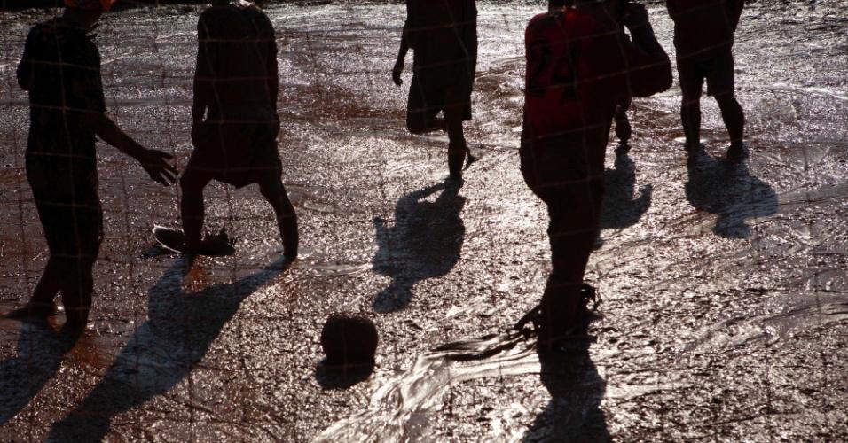 Jogadores disputam bola dutante cometição de futebol na lama em Pequim, na China