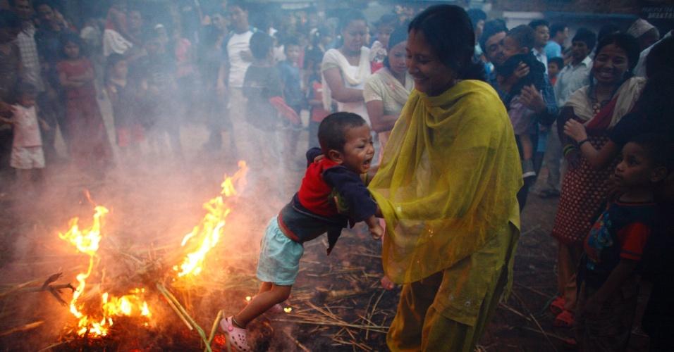 """17.jul.2012 - Criança chora ao ser colocado por sua mãe ao redor do fogo que simboliza a """"destruição do mal"""" durante o festival Ghantakarna, na antiga cidade de Bhaktapur, no Nepal"""