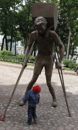"""17.jul.2012 - Criança olha para escultura viva denominada """"Torre de Neve"""" do artista cubano-americano Enrique Martinez Celaya, em São Petersburgo (EUA)"""