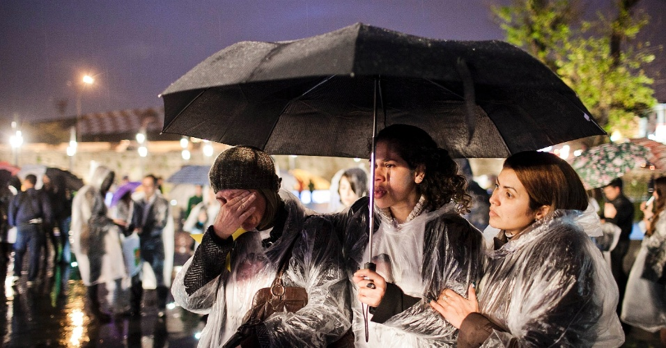 17.jul.2012 - Debaixo de chuva, familiares e amigos fazem um minuto de silêncio para relembrar as vítimas do voo 3054 da TAM, que se acidentou há cinco anos e deixou 199 pessoas mortas. A tragédia ocorreu em frente ao aeroporto de Congonhas, em São Paulo. Às 18h51, horário exato da explosão do avião contra um prédio da própria companhia, a homenagem foi feita pelas famílias, durante a inauguração da praça batizada de Memorial 17 de Julho, localizada na avenida Washington Luiz, na zona sul de São Paulo, onde ocorreu o acidente