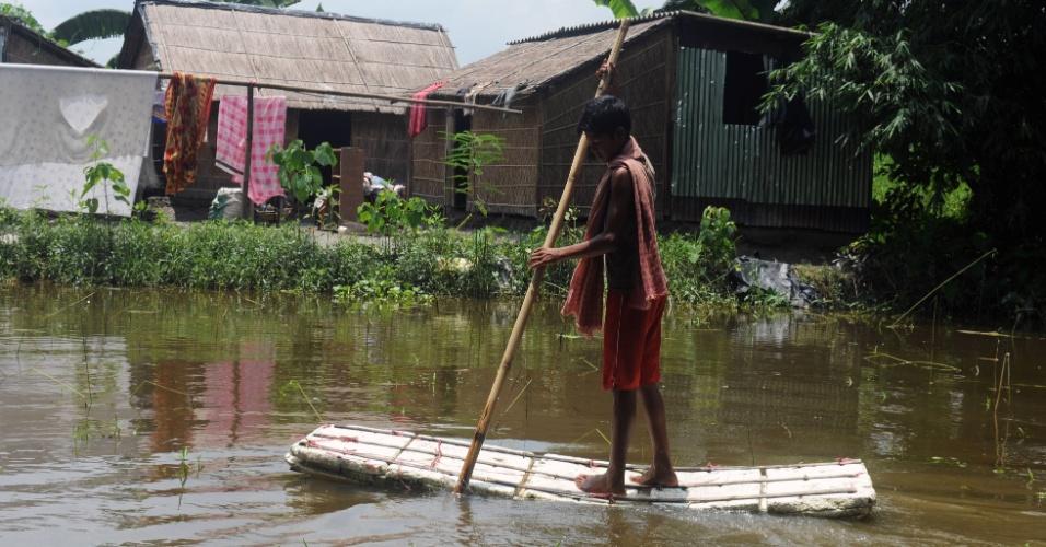 17.jul.2012 - Jovem indiano usa um barco artesanal para se locomover pelas ruas castigadas pelas inundações em Jalpaiguri, na Índia