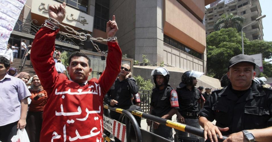 17.jul.2012 - Manifestante egípcio amarra os braços com correntes durante um protesto contra o Tribunal Administrativo do Cairo, no Egito