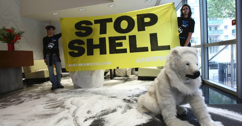 19.jul.2012 - Ativistas do Greenpeace seguram bandeira &#34;Shell Stop&#34; ao lado de outro manifestante vestido de urso polar durante protesto na sede da Companhia Shell em Colombes, Fran&#231;a. O protesto foi organizado para exigir que as empresas petrol&#237;feras interromper seus planos de explora&#231;&#227;o no &#193;rtico