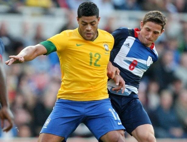 Atacante Hulk é marcado pelo britânico Allen durante amistos da seleção brasileira na Inglaterra