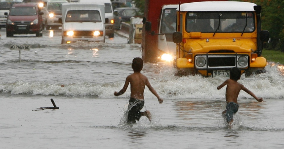 21.jul.2012 - Crian&#231;as brincam em rua inundada pelas fortes chuvas que castigam as Filipinas neste s&#225;bado (21), em Manila