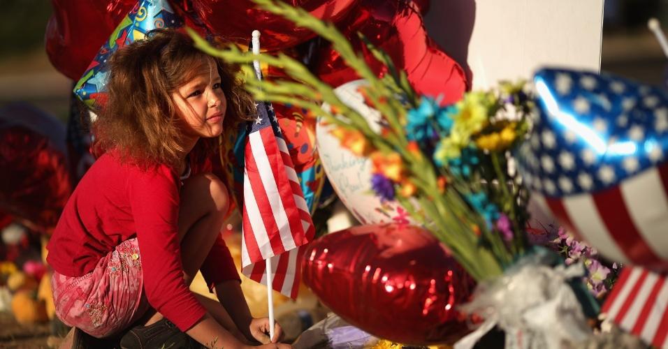 """22.jul.2012 - Criança coloca uma bandeira dos Estados Unidos em memorial improvisado para as vítimas do tiroteio em cinema em Aurora, Colorado (EUA). James Holmes, 24, suspeito de ser o autor do massacre está sendo mantido em uma solitária """"para sua própria proteção"""", segundo o departamento de polícia"""