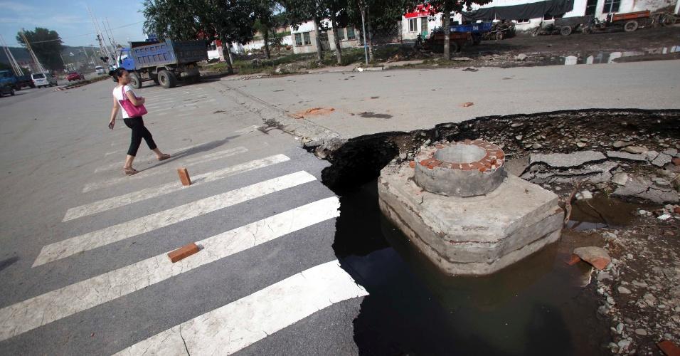 22.jul.2012 - Mulher caminha perto de cratera aberta em uma avenida no distrito de Fangshan, em Pequim, na China, provocada pela forte tempestade deste sábado, a mais forte das últimas seis décadas no país. Ao menos 10 pessoas morreram e cerca de 50 mil pessoas tiveram que deixar suas casas sob risco de desabamentos