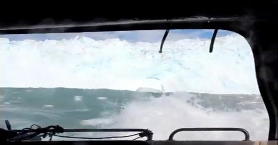 22.jul.2012 - O desmoronamento de um pedaço de iceberg formou uma grande onda que ameaçou engolir um barco ao largo da costa da Groenlândia
