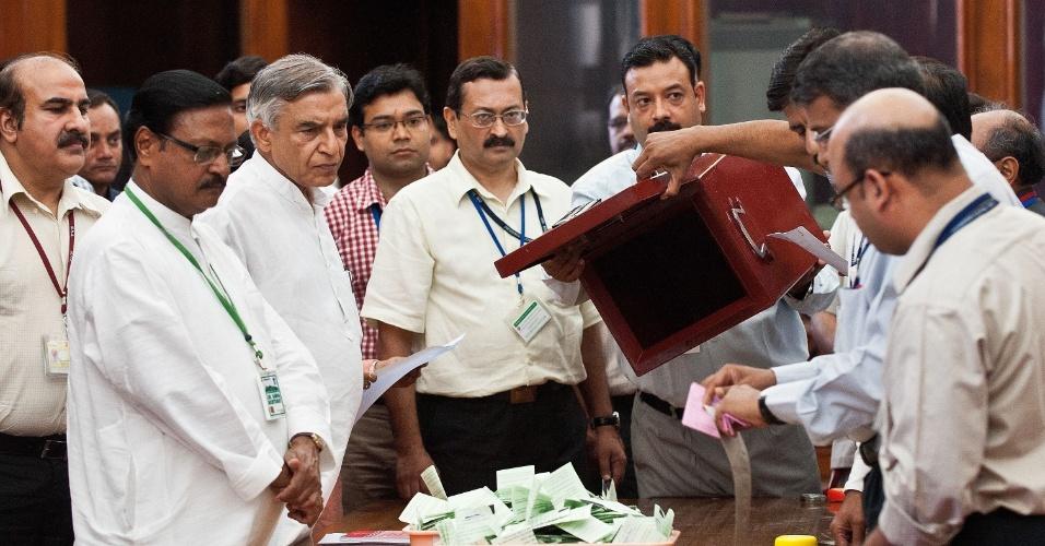 22.jul.2012 - Observadores eleitorais esvaziam urna em Nova Déli (Índia), durante apuração do resultado das eleições presidenciais