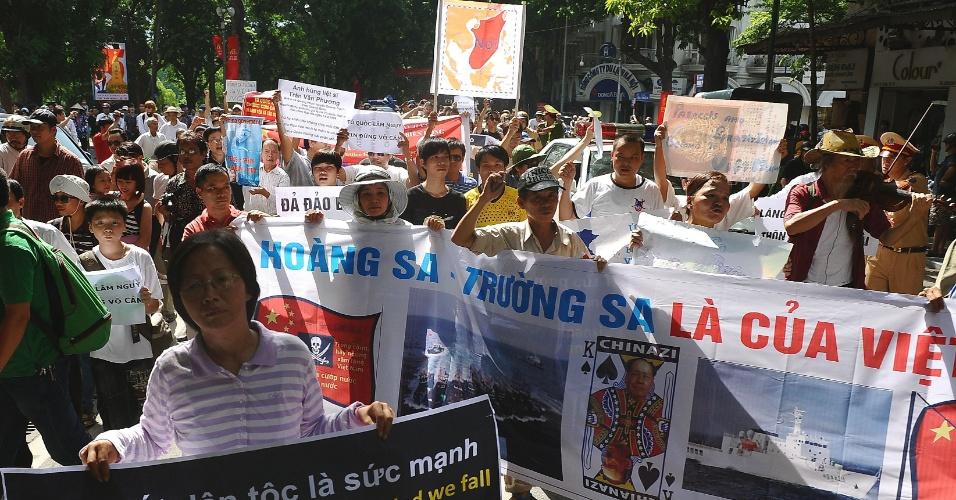22.jul.2012 - Segurando faixas e cartazes e gritando palavras de ordem anti-China, manifestantes marcham em direção à sede da embaixada chinesa, no centro de Hanói (Vietnã), neste domingo (22)