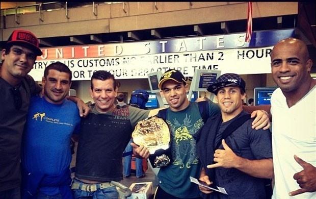Renan Barão, novo campeão do UFC, posa com o rival Urijah Faber no aeroporto em Calgary, após conquistar o cinturão interino dos galos