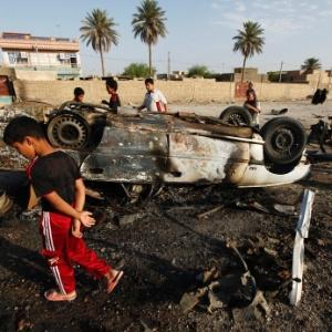 Pessoas observam carro-bomba que explodiu em Mahmudiya, ao sul de Bagdá, no Iraque