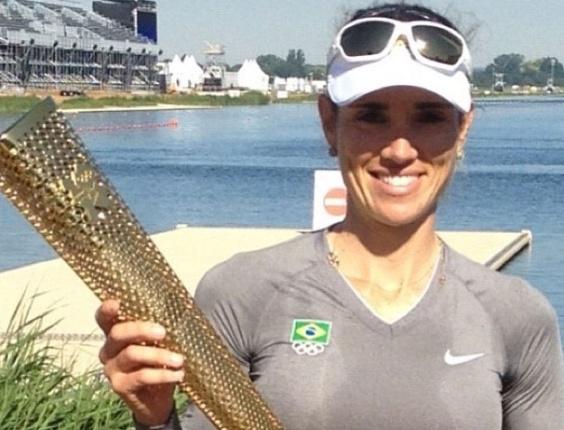 Brasileira Fabiana Beltrame posa com uma réplica da tocha olímpica no centro de treinamento do remo (23/07/2012)
