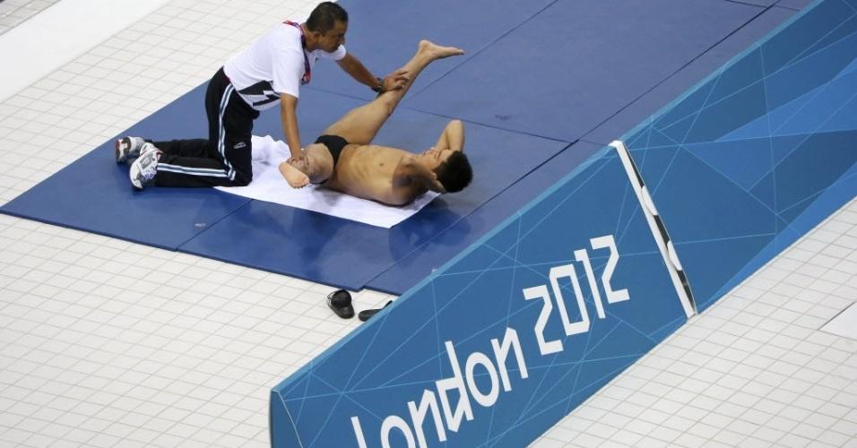 Médico Juan Antonio Avila Gordillo alonga o mergulhador mexicano Yahel Castillo em treino para a Olimpíada de Londres (23/07/2012)