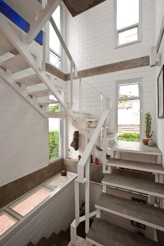 No Residencial Vila Maida, as escadas que seguem para pavimentos superiores são estruturadas em aço, com degraus feitos de chapa metálica, preenchida com concreto e finalizada com cimento queimado. O projeto arquitetônico da