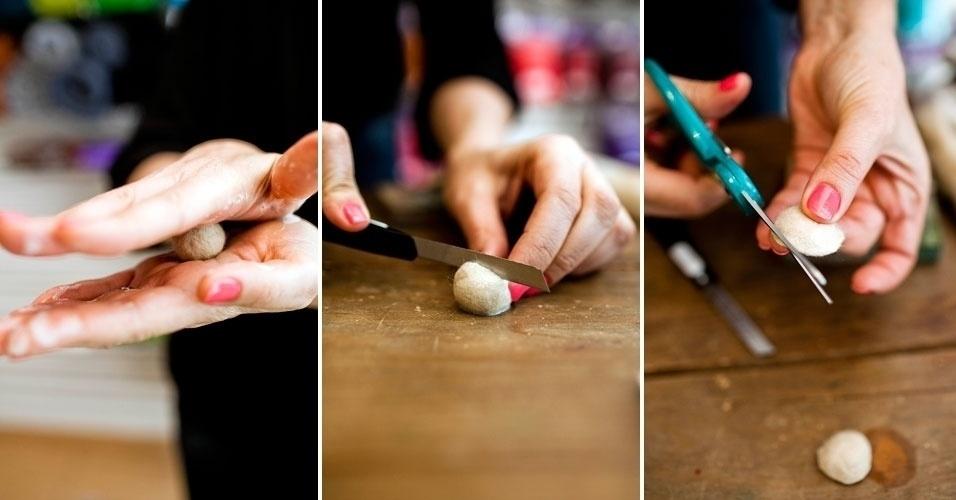 Role a esfera de lã mais um pouco na mão até ficar dura. Corte no meio com o estilete, que resultará em duas cabecinhas. Apare-as com a tesoura