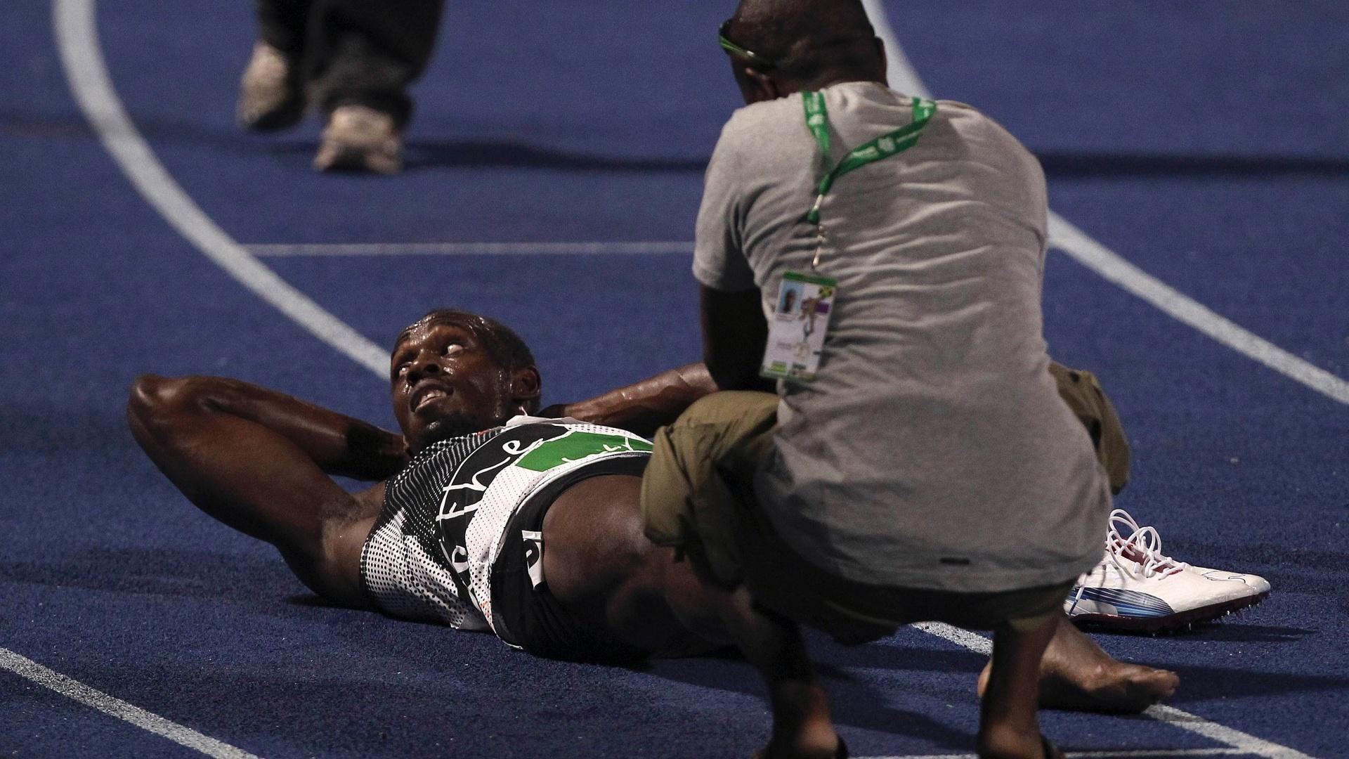 Usain Bolt recebe massagem na perna direita após perder a final dos 200 m na seletiva olímpica jamaicana (01/07/2012)