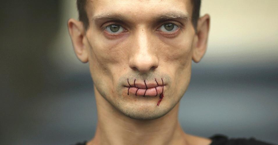 """24.jul.2012 - Imagem divulgada nesta terça-feira (24), mostra o artista Pyotr Pavlensky com a boca costurada em frente à catedral de Kazan, em São Petersburgo, na Rússia, na segunda-feira (23). Ele protesta contra a prisão das das integrantes da banda punk feminina """"Pussy Riot"""""""