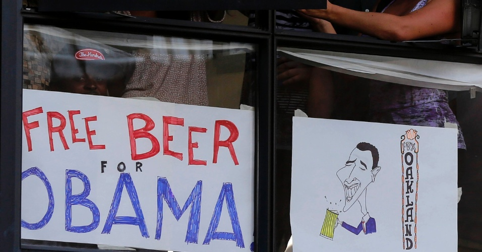 """24.jul.2012 - Moradores de Oakland, nos EUA, mostram cartaz onde se lê """"Cerveja de graça para Obama"""". O presidente norte-americano fez campanha na cidade nesta segunda-feira (24)"""