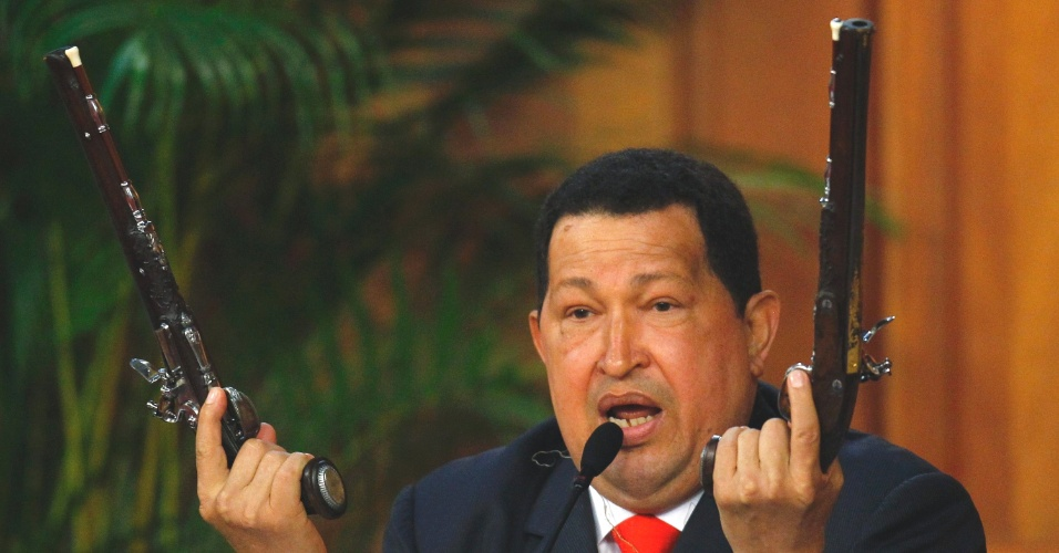 24.jul.2012 - O presidente da Venezuela, Hugo Ch&#225;vez, mostra as pistolas que Simon Bol&#237;var teria usado nas guerras de inedpend&#234;ncia do pa&#237;s. Ch&#225;vez mostrou ao p&#250;blico as pistolas e um retrato de Bol&#237;var na celebra&#231;&#227;o do anivers&#225;rio do her&#243;i nacional, nesta ter&#231;a-feira (23), em Caracas
