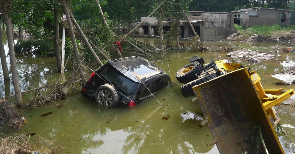 24.jul.2012 - Um carro e um trator ficaram parcialmente submersos em um campo de cultivo inundado na aldeia de Dongnanzhang, no distrito de Fangshan, em Pequim (China). A tempestade mais forte em 60 anos, que atingiu a capital chinesa na segunda-feira (24), deixou mais de 30 mortos
