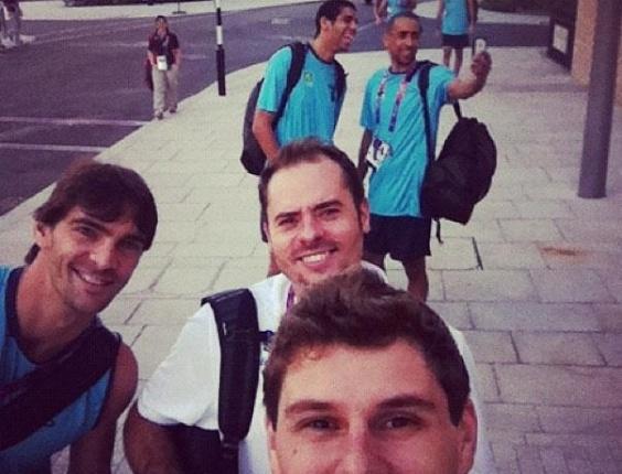 Bruninho, levantador da equipe masculina de Vôlei, tira foto dentro da Vila Olímpica, junto com Giba e Ricardinho; ao fundo, vemos Wallace e Serginho