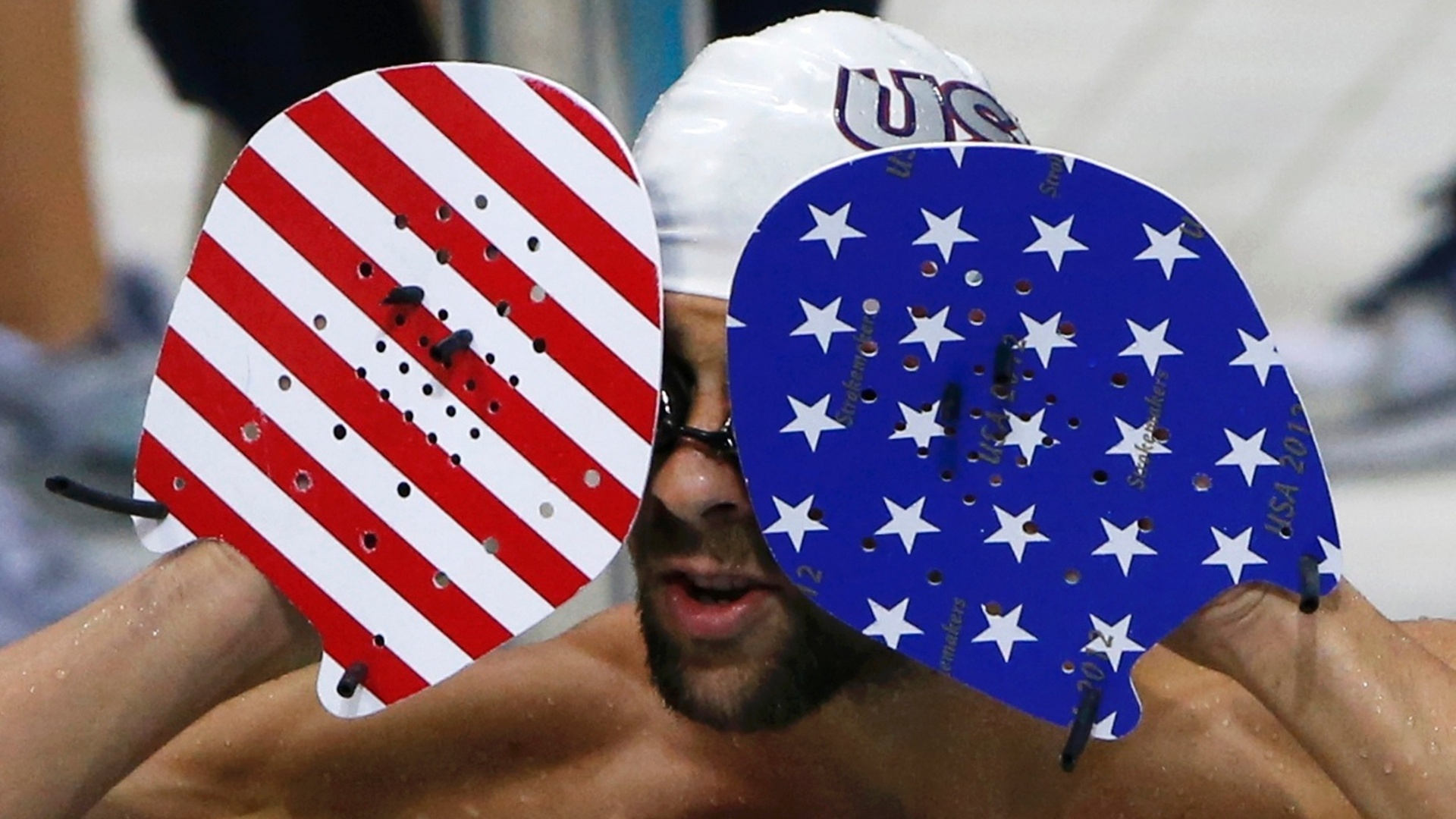 Michael Phelps tenta remover seus culos de natao enquanto usa equipamento nas cores da bandeira dos EUA (24/07/2012)