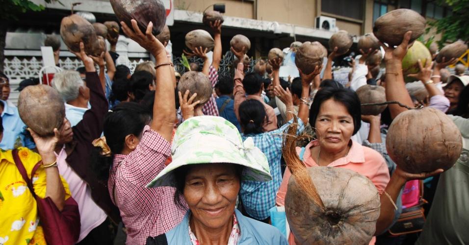 26.jul.2012 - Agricultores seguram cocos em frente à sede do Governo em Bancoc, na Tailândia, nesta quinta-feira (26). Eles querem que o preço da fruta seja elevado de 2 bahts (R$ 1,20) para 15 baths (R$ 9)