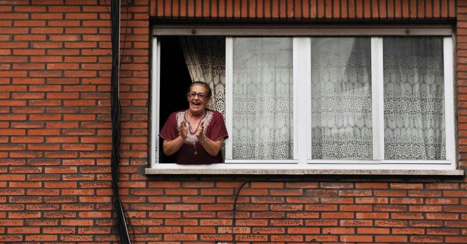 26.jul.2012 - Da janela, mulher aplaude a passagem de manifestantes do setor de mineração na cidade de Gijon, na Espanha. Eles protestam contra o corte de investimentos do governo no setor