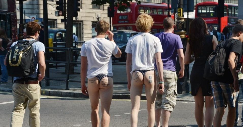 26.jul.2012 - Dois homens caminham pelas ruas do centro de Londres, no Reino Unido, com publicidade nas nádegas