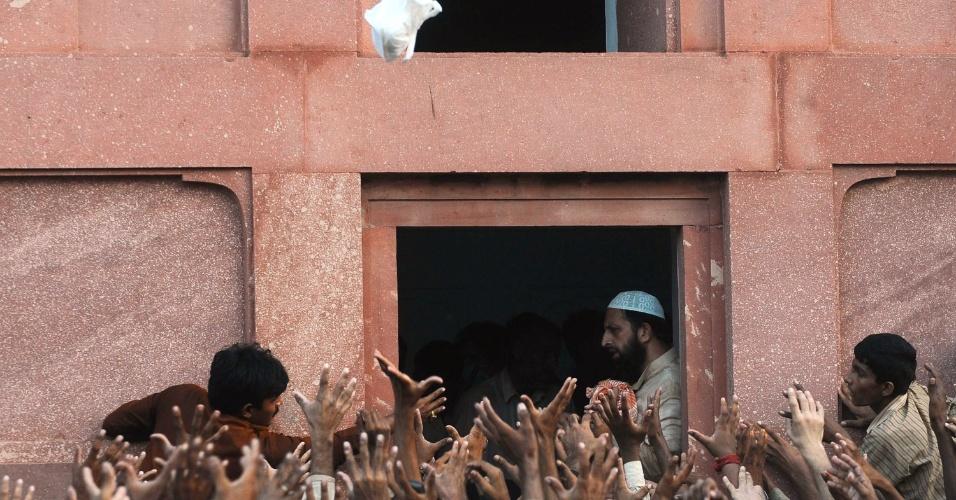 26.jul.2012 - Homens tentam pegar uma sacola de comida atirada em Lahore, no Paquistão, pouco antes do pôr do sol. Durante o mês sagrado do Ramadã, os muçulmanos fazem jejum do amanhecer ao anoitecer