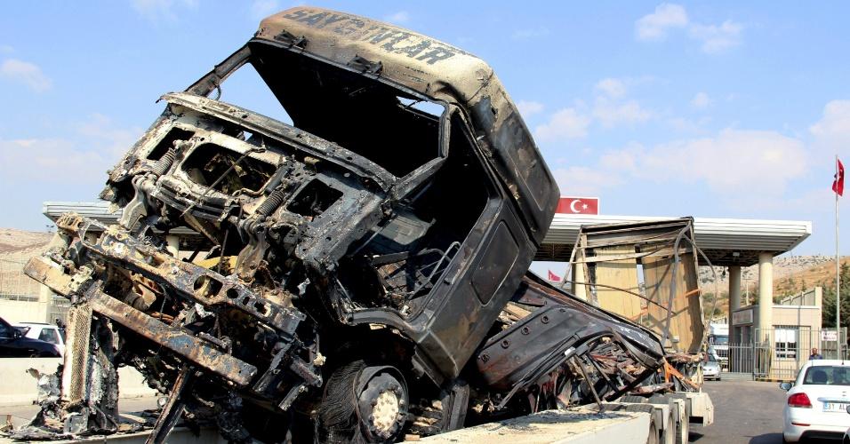 """26.jul.2012 - Imagem divulgada nesta quinta-feira (26), mostra veículo de carga transportando caminhão destruído durante conflitos no noroeste da Síria, na terça-feira (24), no posto de fronteira de Reyhanli (na divisa entre Turquia e Síria). Rebeldes afirmaram hoje (26) que assumiram o controle de """"quase a metade"""" de Aleppo, capital econômica da Síria"""