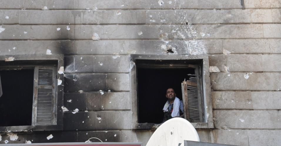 26.jul.2012 - Membro das forças rebeldes da Síria olha através da janela em Aleppo, no norte do país, nesta quarta-feira (25)