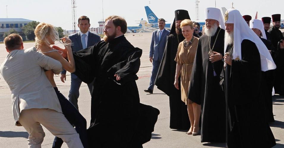 26.jul.2012 - Seguranças detêm ativista do grupo feminista Femen nesta quinta-feira (26) durante protesto contra a visita do chefe da Igreja Russa Ortodoxa, o Patriarca Kirill (à direita), à Ucrânia, no aeroporto Borispol, perto da capital, Kiev