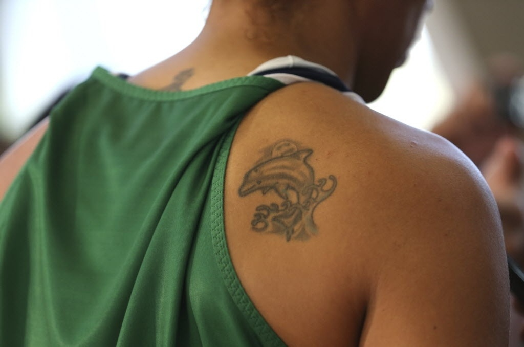 Cheia de pequenas tatuagens, rika, do basquete, tem um golfinho desenhado nas costas