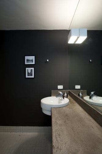 No banheiro do Apartamento 43, em São Paulo, a bancada de concreto é combinada a um amplo espelho, parede escura e chão revestido por pastilhas foscas. O projeto de interiores do apê é assinado por Marcel Steiner