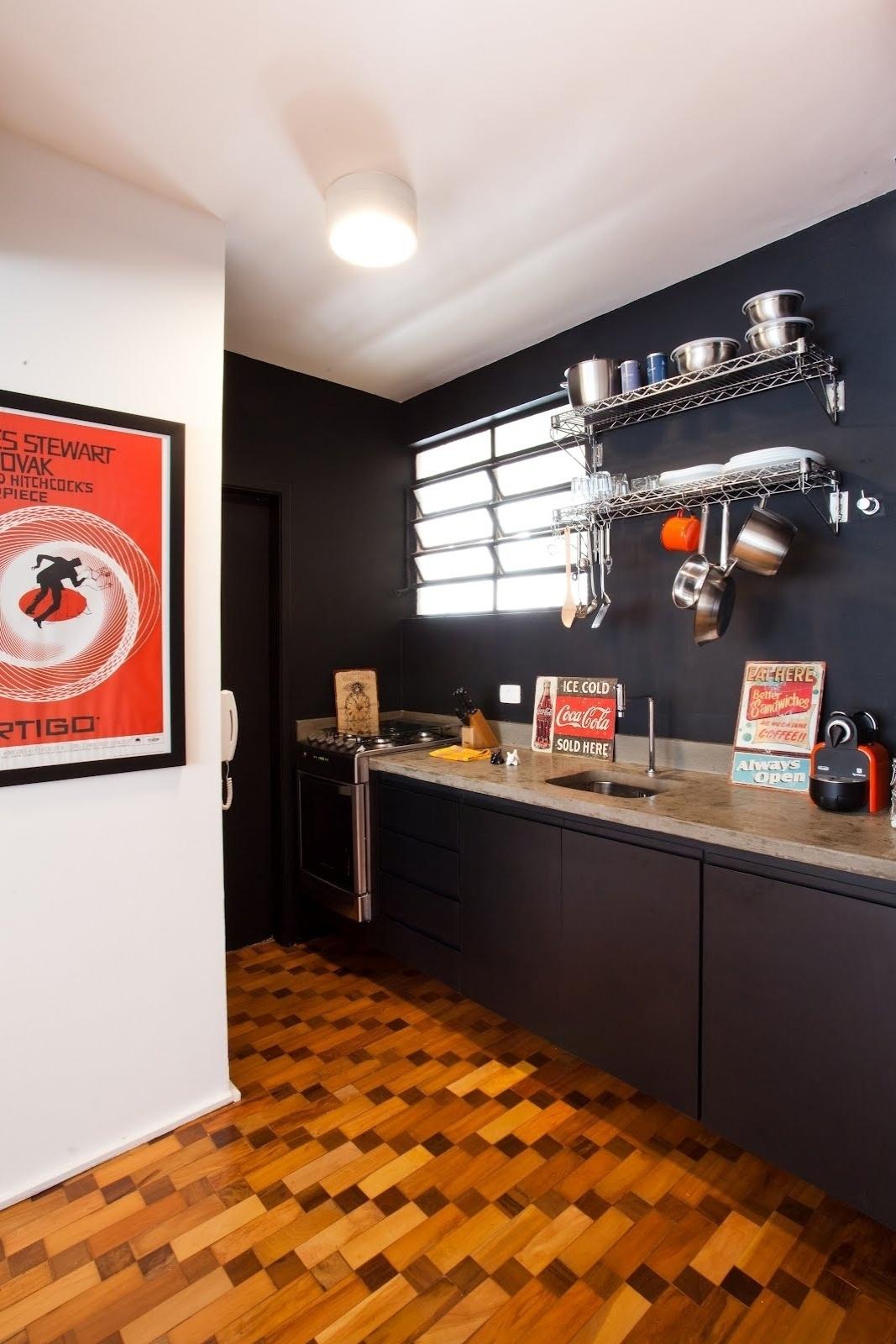 O esmalte fosco na cor preta recobre parte das paredes da cozinha do Apartamento 43, em São Paulo. A marcenaria do ambiente também recebeu tratamento escuro que, segundo o designer de interiores Marcel Steiner, garante aconchego ao espaço. Pôsteres de filmes, como o hitchcockiano