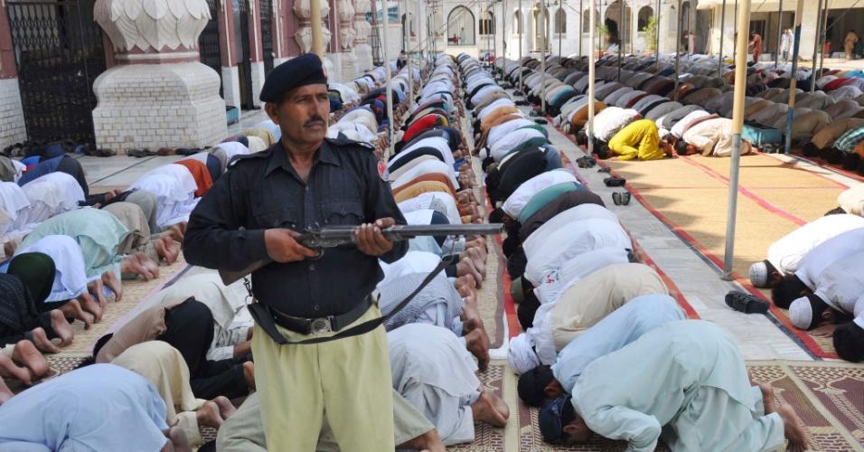 27.jul.2012 - Soldado monta a guarda enquanto muçulmanos atendem às preces desta sexta-feira (27) durante o Ramadã, o mês sagrado do Islamismo, em Faisalabad, no Paquistão