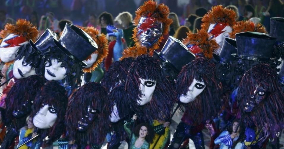 Artistas carregam máscaras representativas dos astros do rock inglês durante cerimônia de abertura