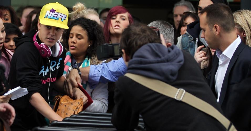 Justin Bieber é cercado por fãs ao desembarcar no aeroporto de Heathrow, em Londres (23/3/12)